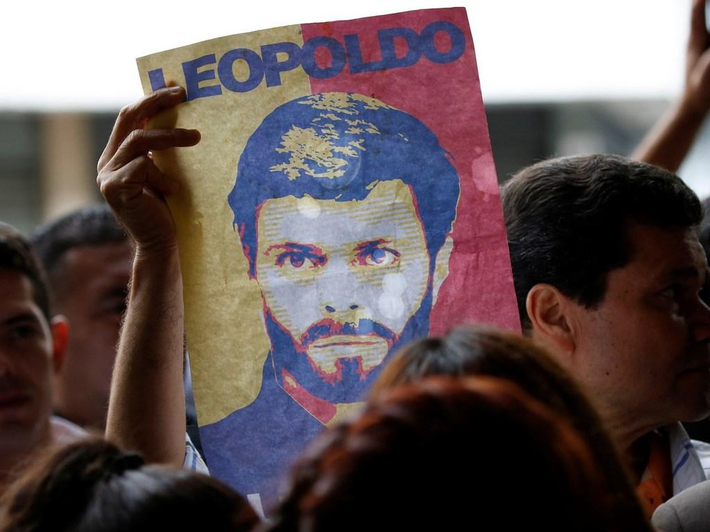 Prosvjednik drži znak za potporu uhićenom vođi Venezuelske opozicije Leopoldu Lopezu. Reuters